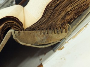 Side view of scrapbook showing unusual binding material.